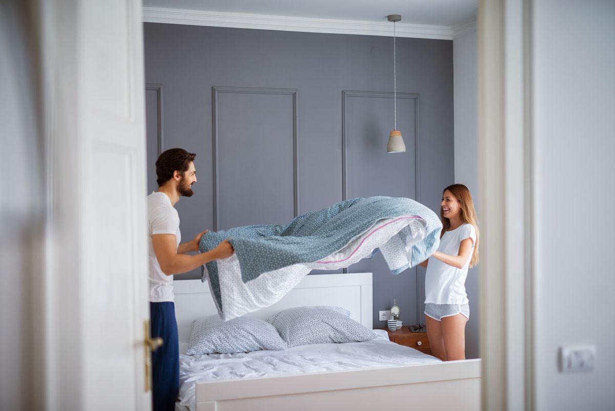 Un cuplu zâmbitor, surprinși în dormitor, în timp ce își fac patul