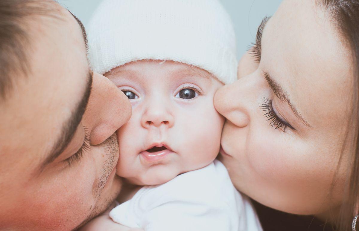 Mama și tata își sărută bebelușul, fiecare pe câte un obraz