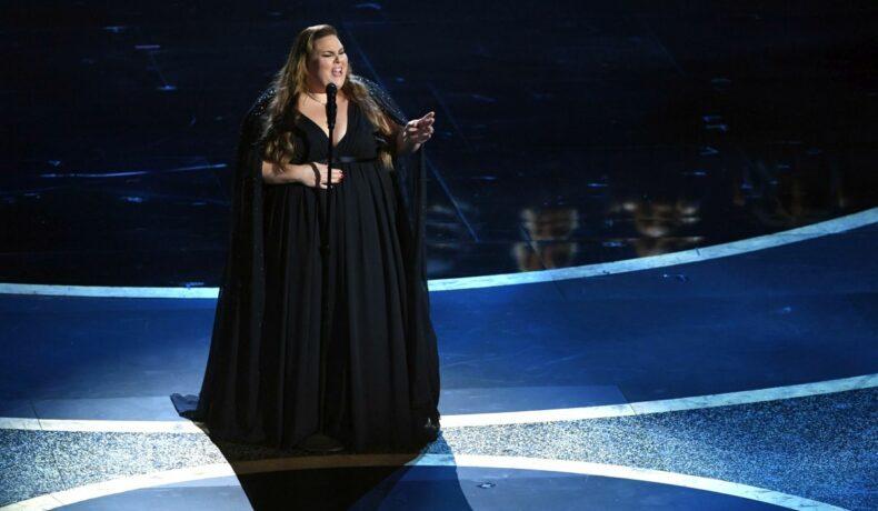 Chrissy Metz, îmbrăcată într-o rochie neagră, de gală, vorbește în fața unui microfon