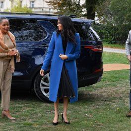 Doria Ragland alături de fiica sa Meghan Markle și Prințul Harry îmbrăcată în pantaloni și bluză de culoare crem, la o lansare de carte de bucate în Londra
