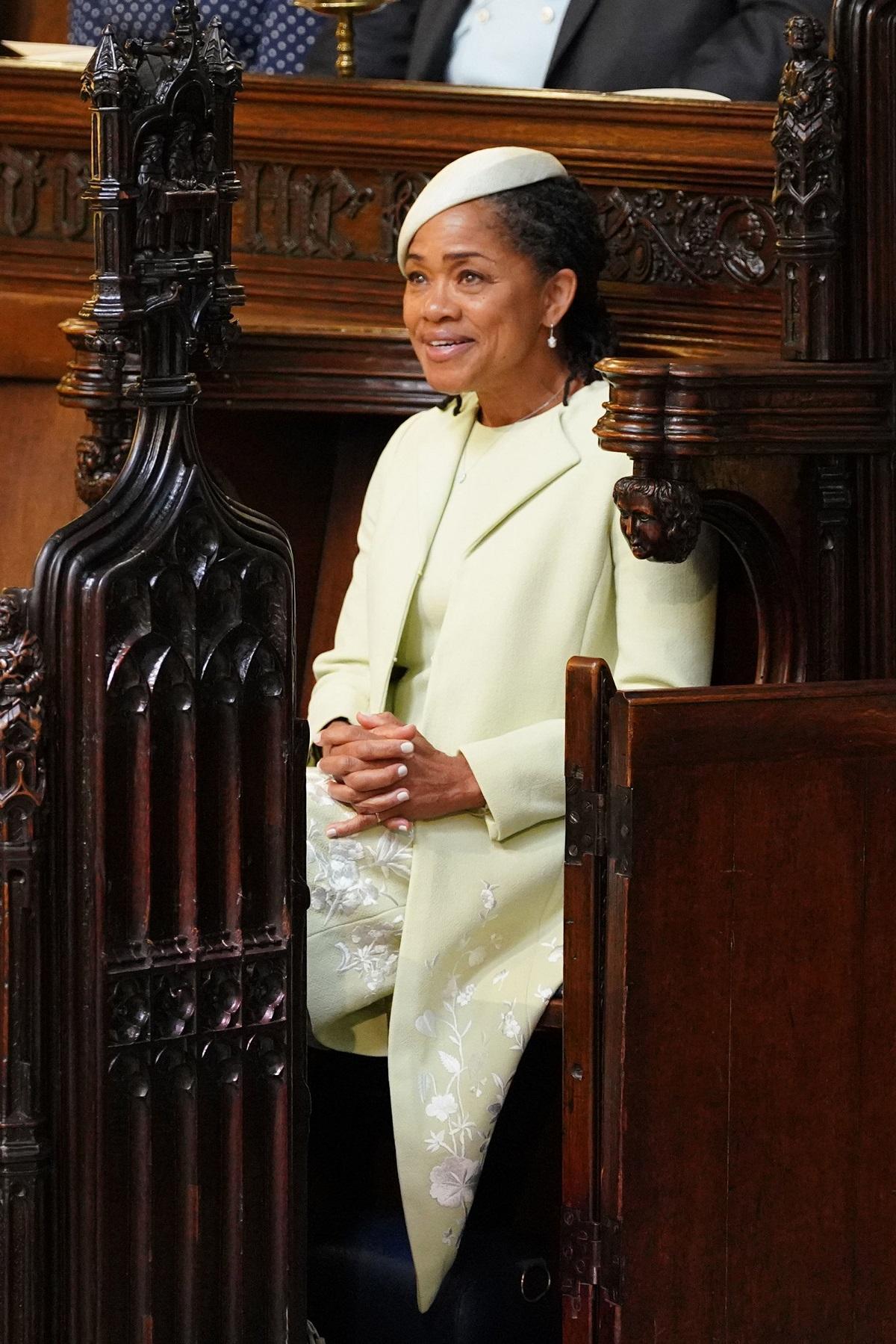 Doria Ragland îmbrăcată într-un costum alb în timp ce stă jos pe un scaun din Capela St George în timp ce așteaptă începerea ceremoniei de la nunta Prințului Harry cu fiica sa Meghan Markle în data de 19 mai 2018