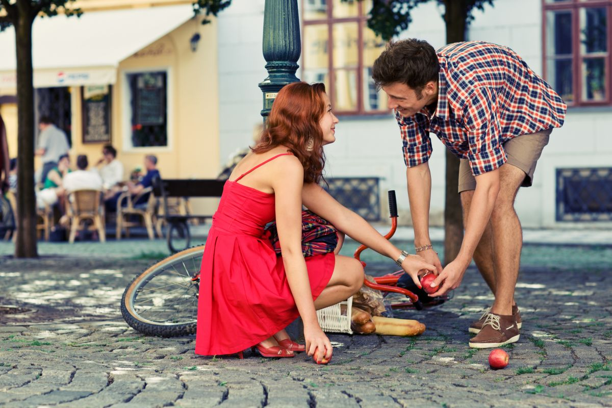 Un bărbat încearcă să o ajute pe o femeie pe stradă să strângă cumpărăturile, după ce plasa ei s-a răsturnat