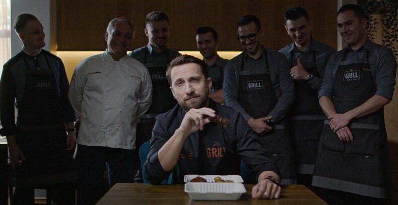 Dani Oțil, la masă, cu mai mulți bucătari în spatele lui