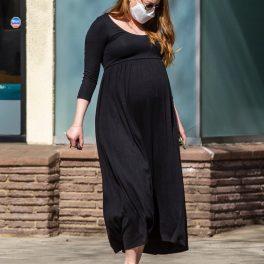 Emma Stone, într-o rochie neagră și sandale maronii, mergând pe stradă