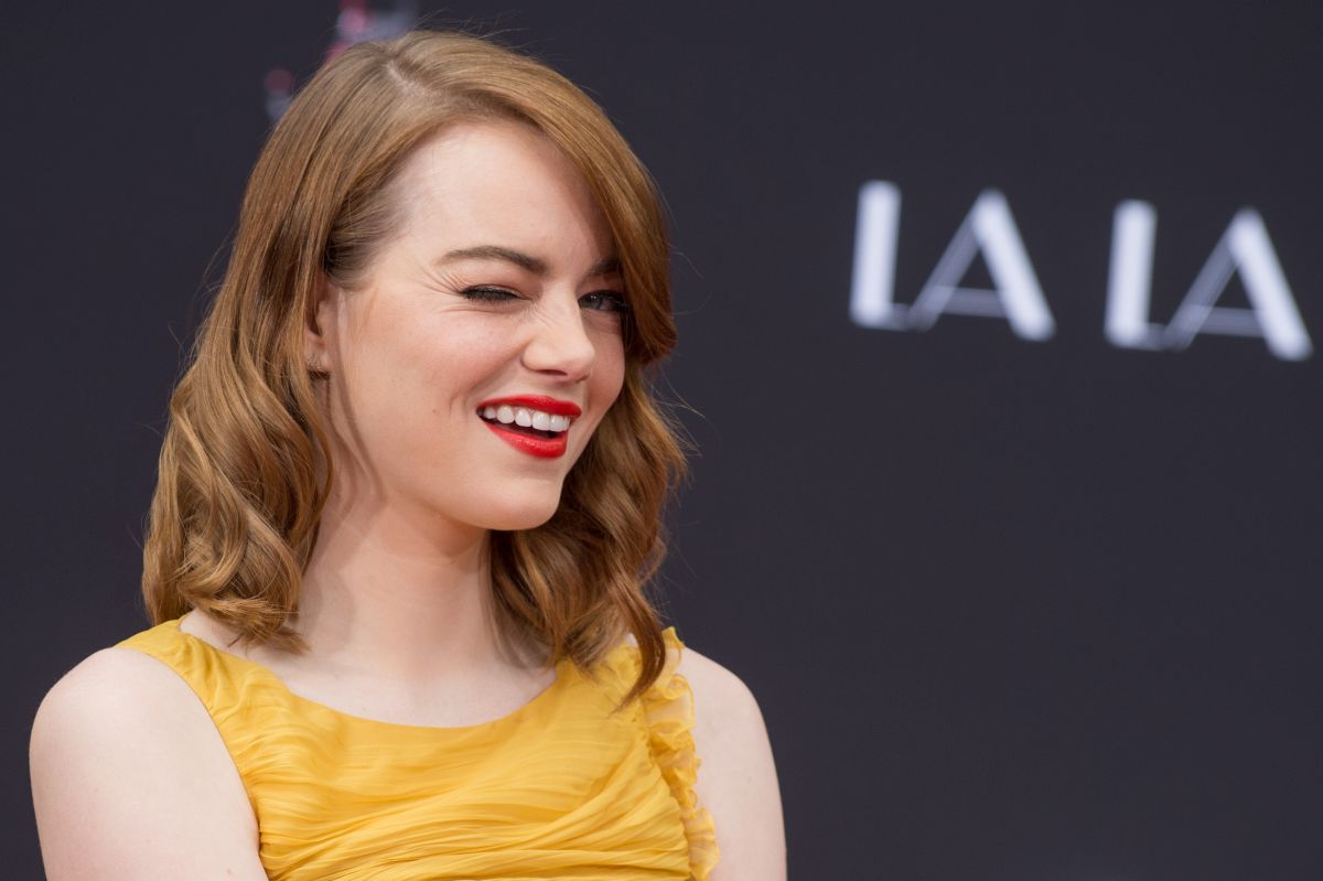 Actrița Emma Stone, îmbrăcată într-o bluză galbenă, ne face cu ochiul