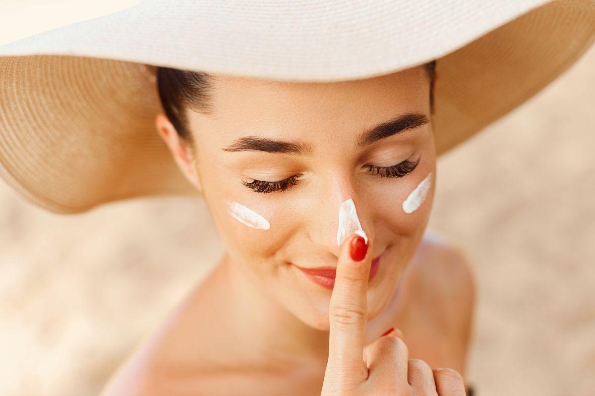 O femei tânără, care poartă pălărie și are cremă de protecție solară pe față, zâmbește