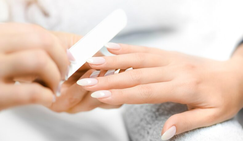 Femeie care își îngrijește unghiile albe cu ajutorul unei pile de unghii, învâțând cum să scape de obiceiurile care afectează sănătatea unghiilor