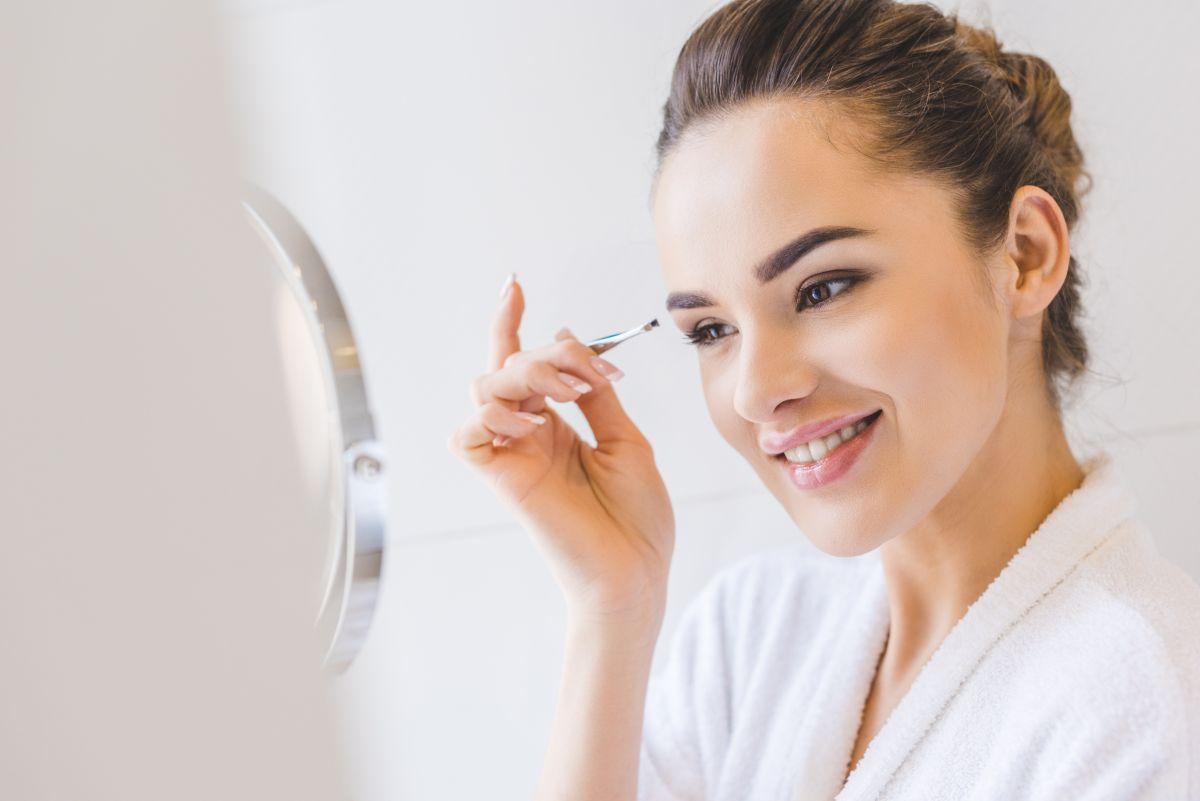 Femeie tănârâ, cu părul prins, într-un halat alb de baie, ce se pensează zâmbind, în oglindă