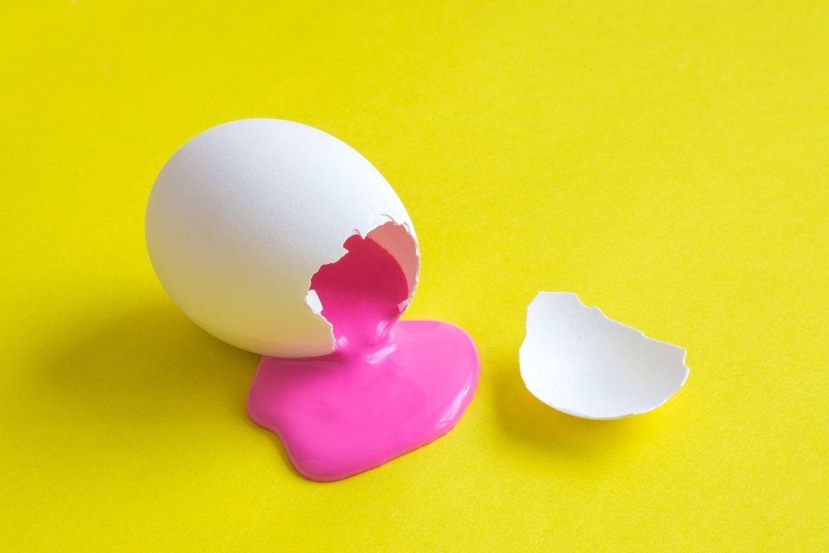 Un ou alb, spart, din care curge vopsea roz, pe un fundal galben