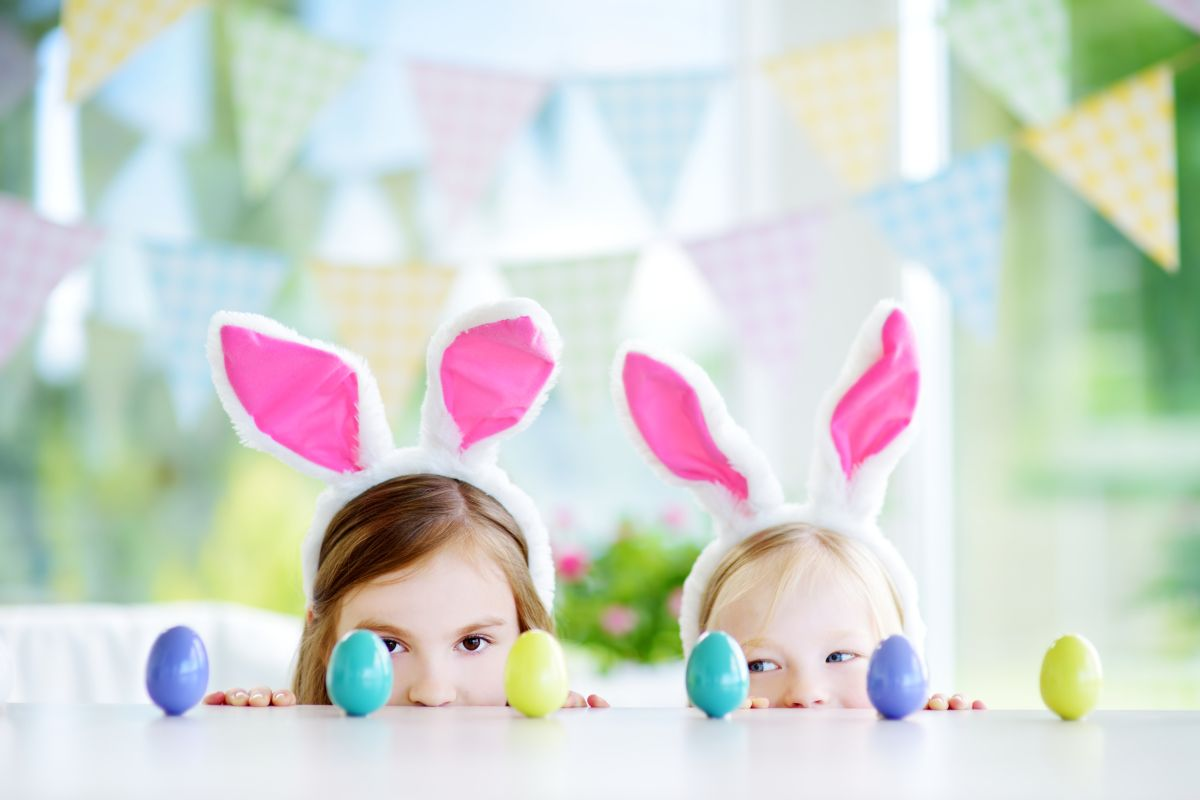 Două fetițe, ce poartă urechi de iepurași, se joacă cu ouă colorate