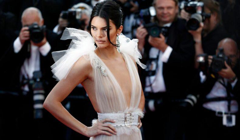 Kendall Jenner, purtând o rochie albă, pozând pentru paparazzi, la un eveniment monden