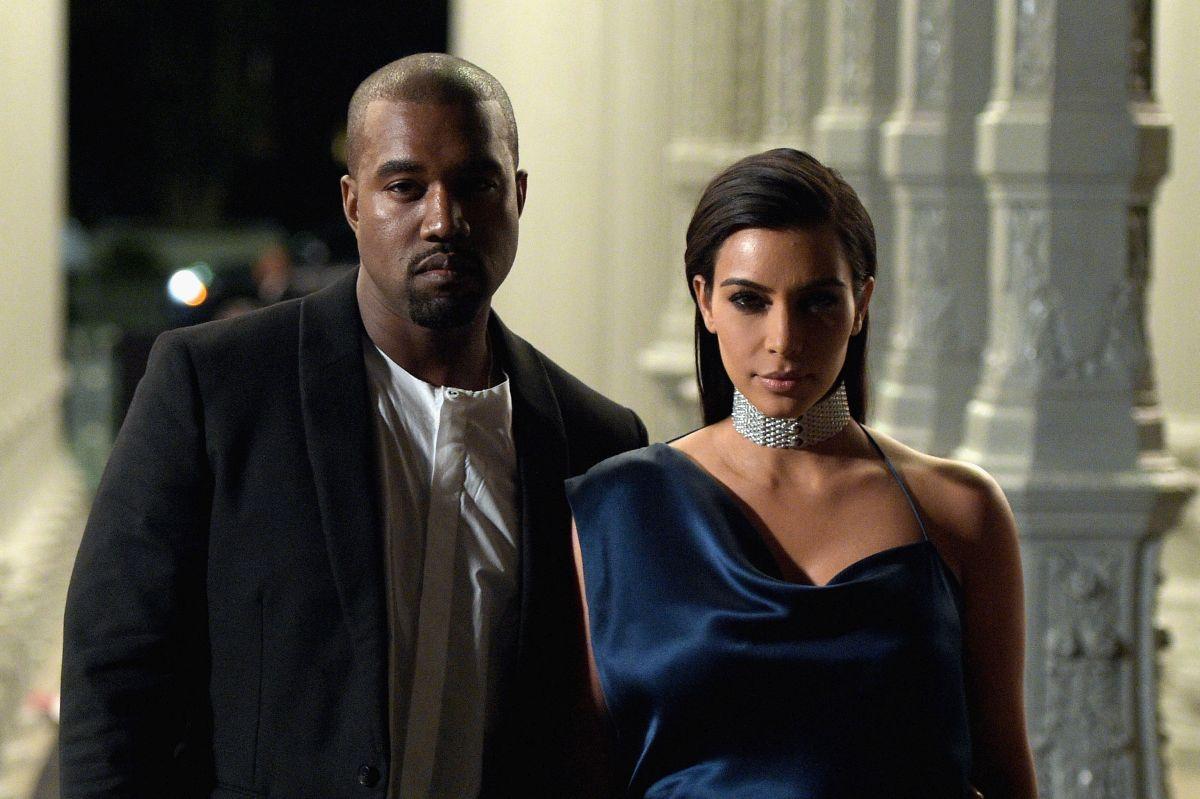 Kim Kardashian îmbrăcată într-o rochie albastră și un colier de diamante la gât, alături de Kanye West, ce poartă o bluză albă și un sacou negru