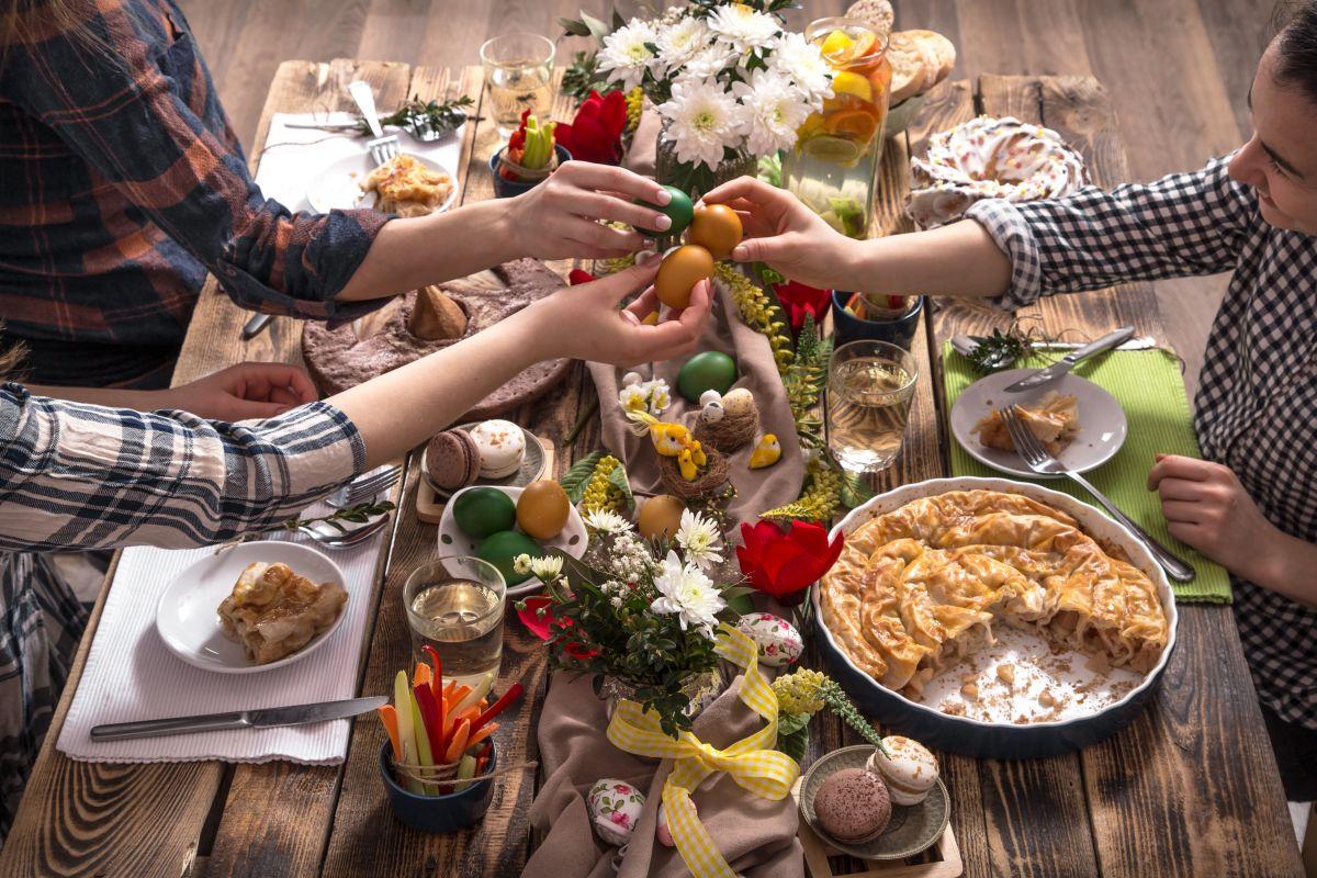 Familia și prietenii, la masa festivă de Paște, ciocnind ouă colorate