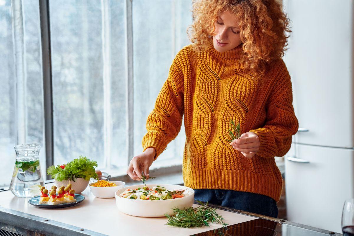 O femeie fericită,îmbrăcată într-un pulover galben, ornează o salată, într-o bucătărie
