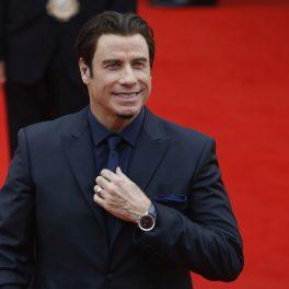 John Travolta, purtând un costum negru, își aranjează cravata, pe covorul roșu
