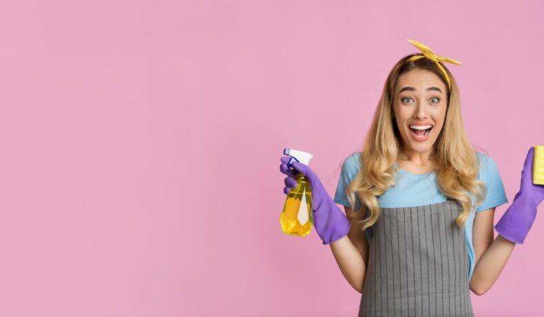 Fată cu părunl lung, ce poartă o bentiță galbenă pe cap și are în mâini un burete de curățat și un spray, pe un fundal roz