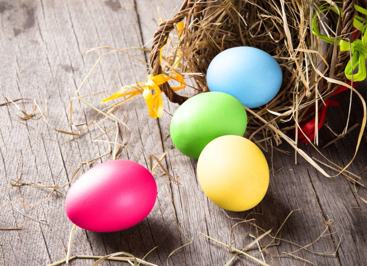 Patru ouă colorate, de Paște, lângă un coș maro, de răchită