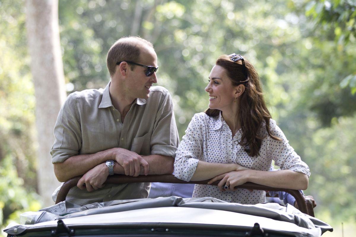 Ducele și Ducesa de Cambridge, zâmbind unul altuia, într-o decapotabilă