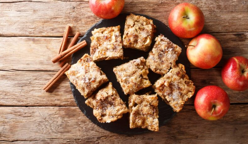 Felii de prăjitură cu mere și scorțișoară, pe un tocător de lemn