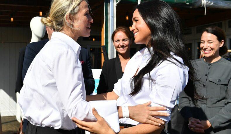Ducesa de Sussex, purtând o cămașă albă, o îmbrățișează pe prietena sa apropiată, Misha Nonoo