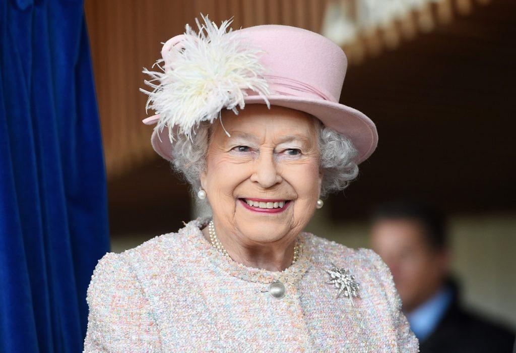 Regina Elisabeta cu o pălarie albă cu pene într-un costum alb în timp ce poartă una din broșele sale celebre numită steaua jardinei
