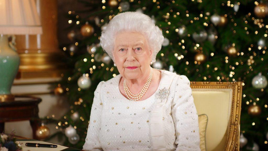 regina elisabeta îmbrăcată într-o ținută albă cu o diademă pe cap în fașa unui brad de Crăciun în timp ce poartă brășa sub formă de stea