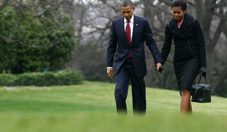 Michelle și Barach Obama, ținându-se de mână, pe o pajiște verde