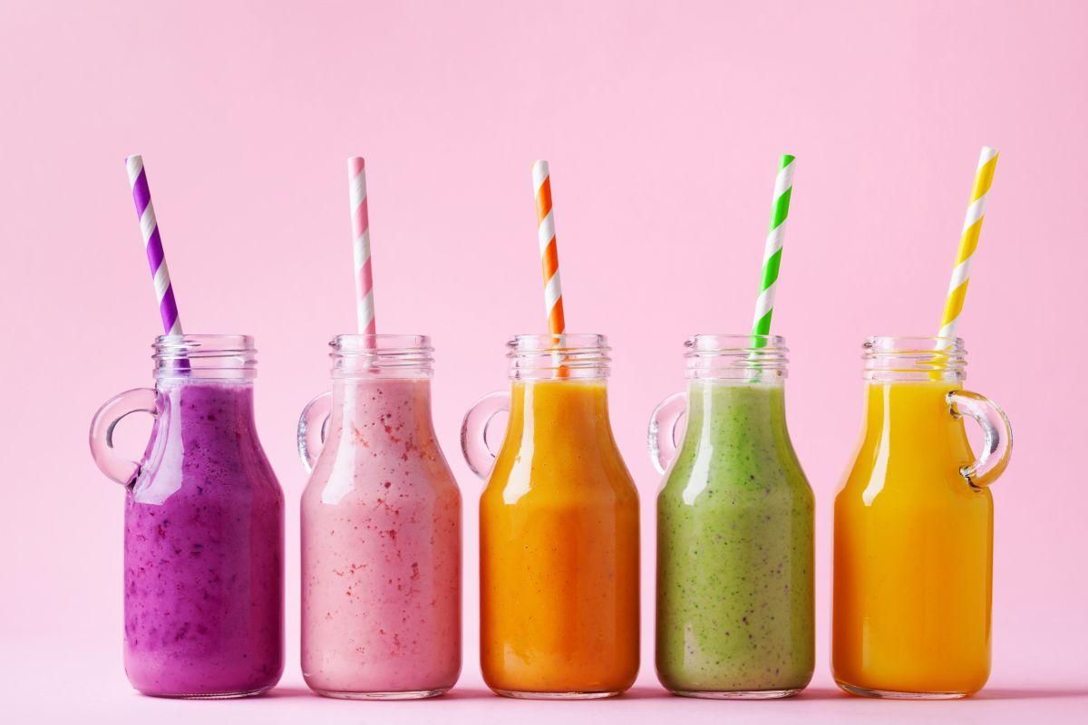 Cinci sticle ce conțin shake-uri colorate de fructe, pe un fundal roz