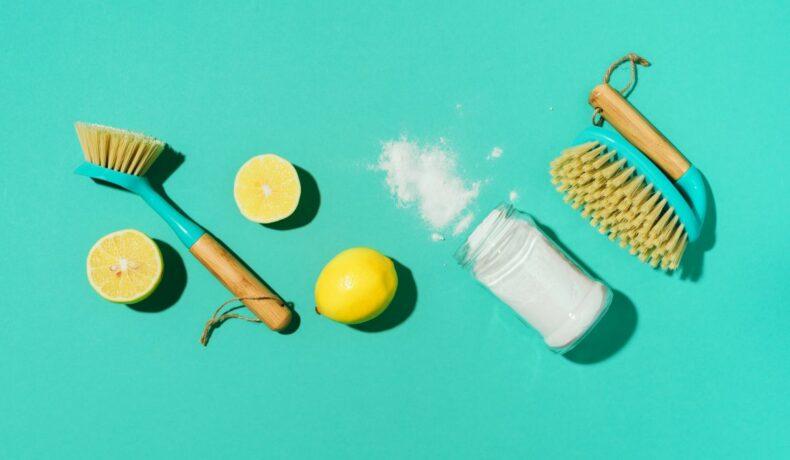 Bicarbonat de sodiu, perii de curățat și lămâie, trioul curățeniei naturale, pe un fundal azur