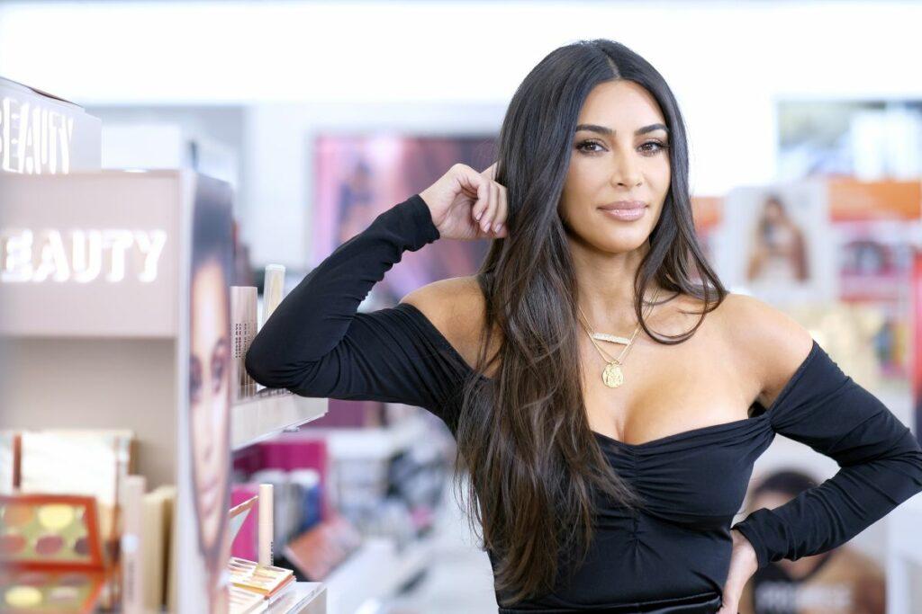 Kim Kardashian, cu o ținută de miliardară, purtând un top de culoare neagră, langă un raft de cosmetice