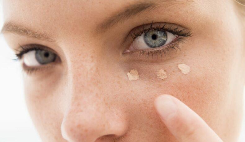 Prim plan al feței unei femei, care își aplică sub zona ochilor trei puncte de fond de ten