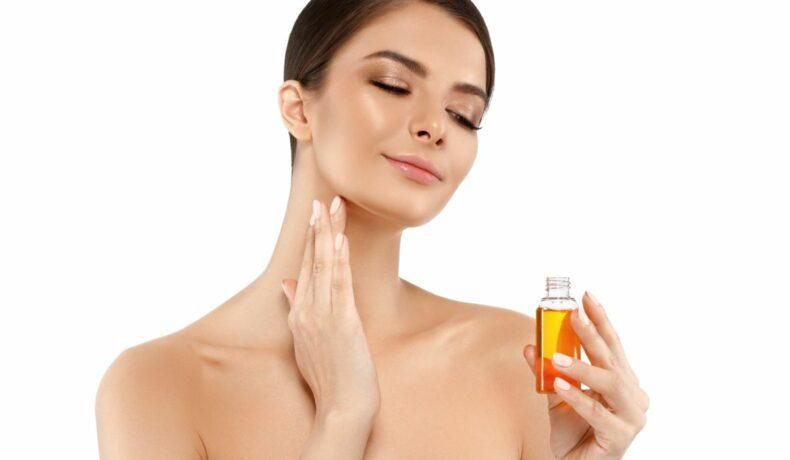 Femeie brunetă, ce ține în mână o sticluță cu ulei, își hidratează pielea