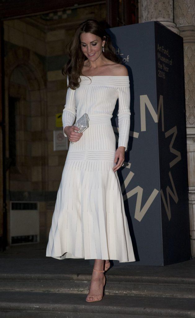Alegerea vestimentară a Ducesei Kate Middleton este o rochie lungă albă cu un decolteu barcă în timp ce coboară scările