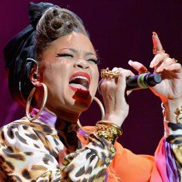 Andra Day, pe scenă, cu un microfon în mână, este coafată, are cerceri rotunzi, mari și buzele sunt de culoare roșie.