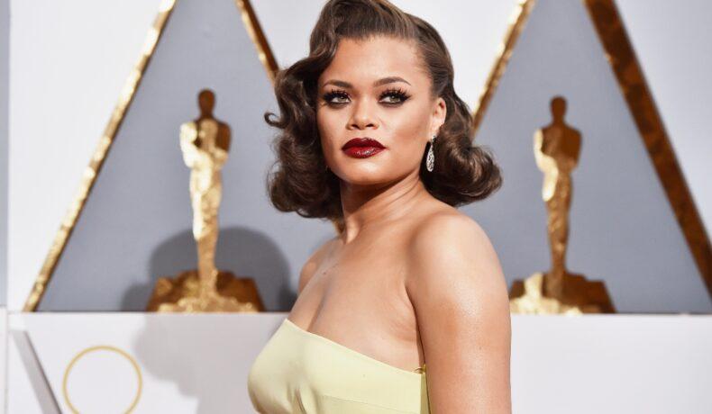 Andra Day îmbracată într-o rochie galbenă, cu părul ondulat, pozează pe covorul roșu la Premiile Oscar din anul 2016.