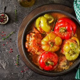 Șase ardei umpluți cu orez și ciuperci, acoperiți cu capacele lor, în sos de roșii