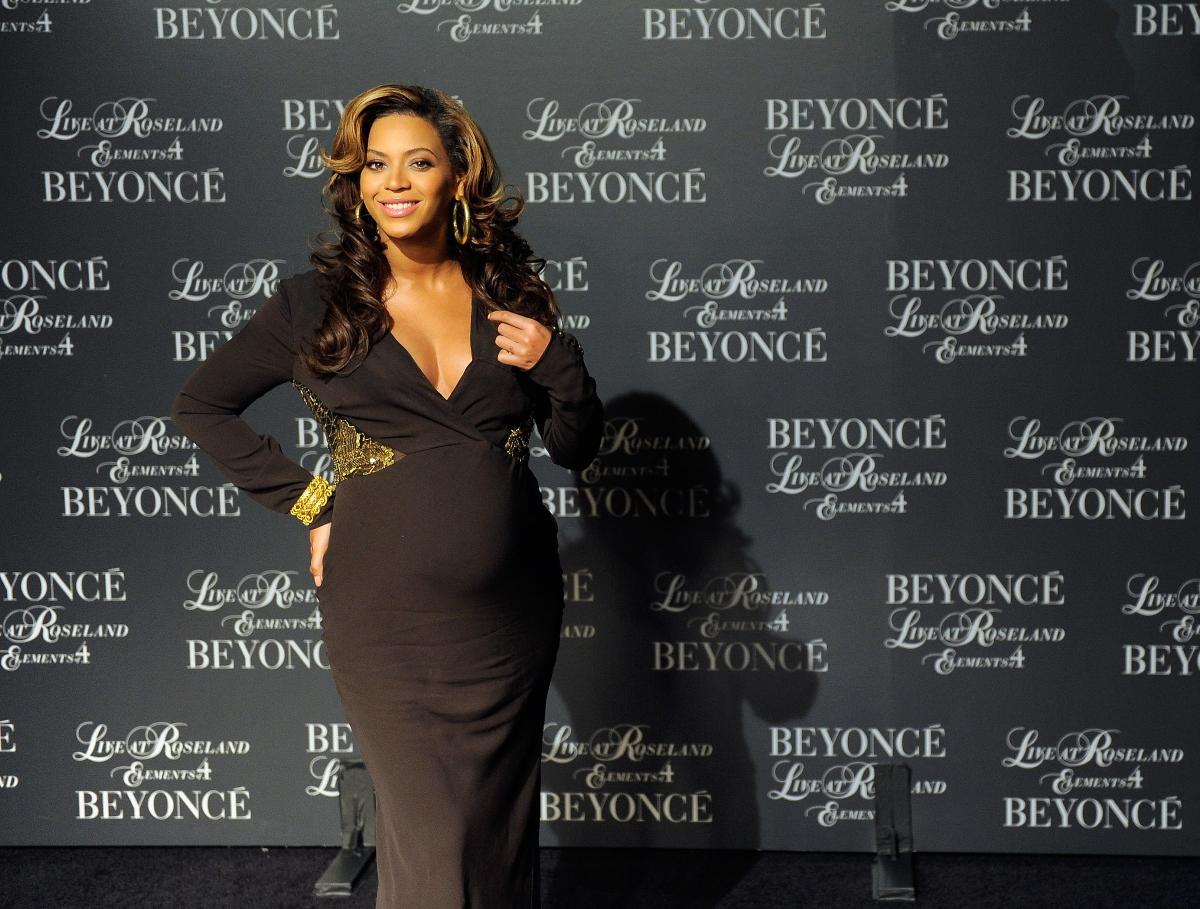 Beyoncé, însărcinată este îmbrăcată într-o rochie neagră, decoltată, cu detalii aurii
