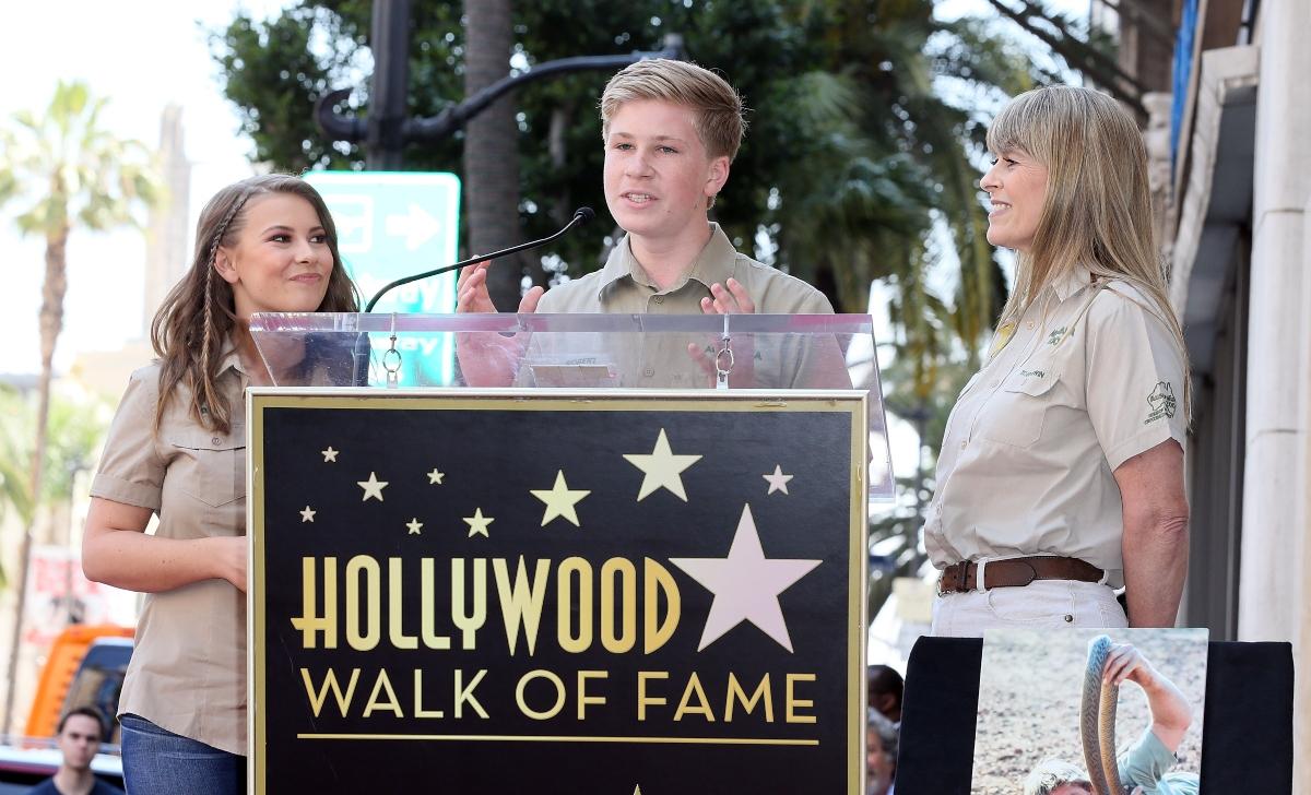 Bindi Irwin poartă o cămașă bej are părul aranjat lejer. Se află alături de mama sa Terri și de fratele său Robert Irwin.