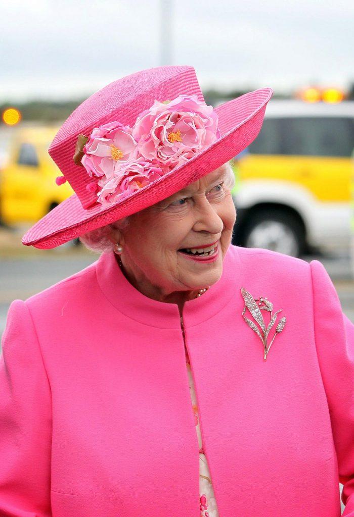 Regina Elisabeta cu o pălărie și un costum roz purtând în piept brosa sa Crinul Londrei