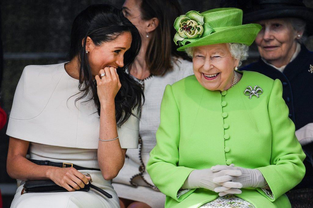Regina Elisabeta purtând una din broșele sale celebre în formă de fundă și îmbrăcată într-un costum verde, alături de ducesa Kate îmbrăcată în alb care îi zâmbește