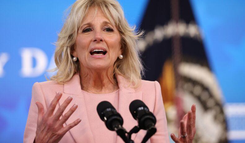 Jill Biden, ține un discurs. În față are două microfoane și gesticulează energic din mâini. Este îmbrăcată într-un costum din două piese, de culoare roz. Are părul blond, aranjat în bucle foarte lejere. Machiajul este discret.