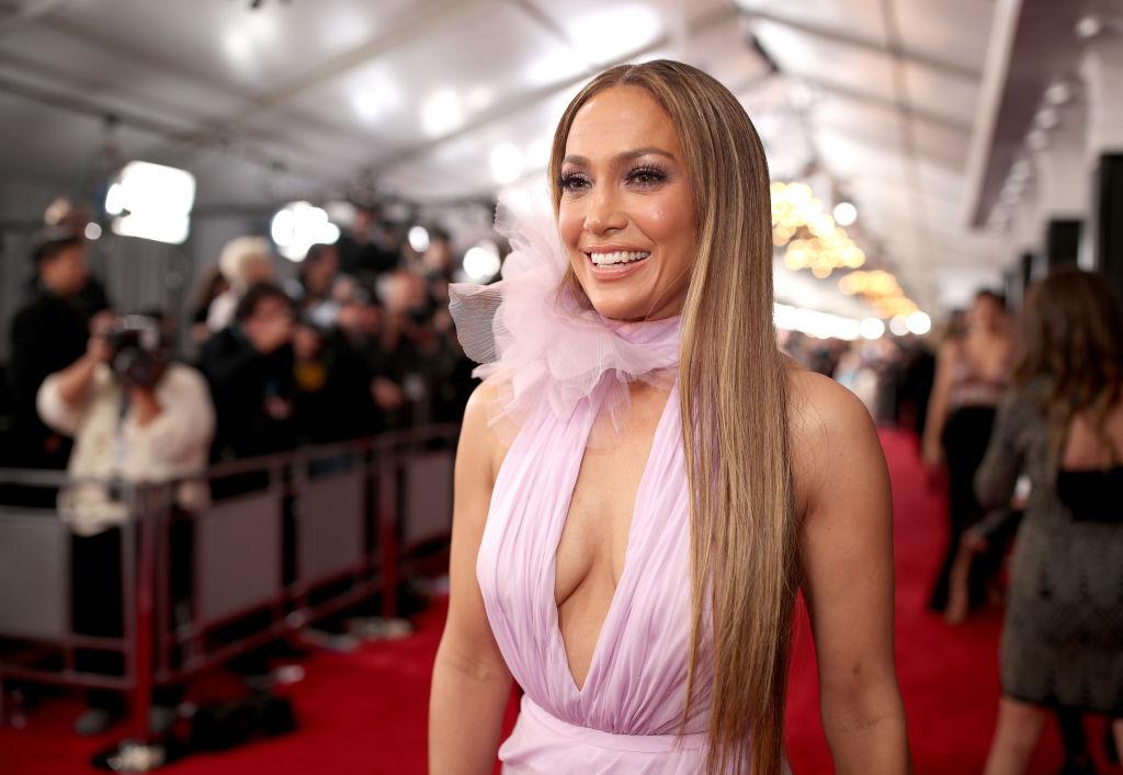Jennifer Lopez, într-o rochie roz, cu volane, pe covorul roșu, la Premiile Grammy