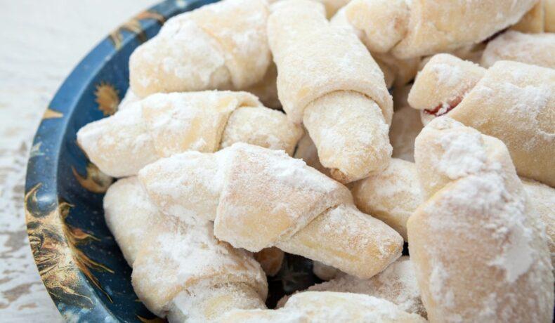 Cornulețe de post umplute cu rahat și pudrate cu zahăr, așezate pe o farfurie albastră.
