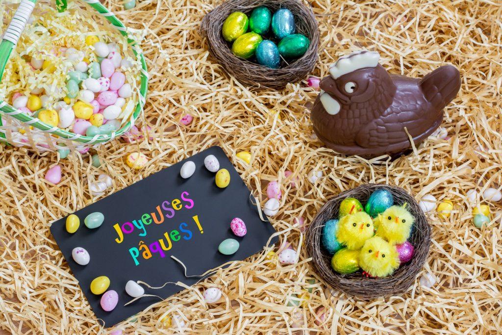 Aranjament cu ouă și puișor de ciocolată, lângă o tăbliță cu un mesaj în franceză