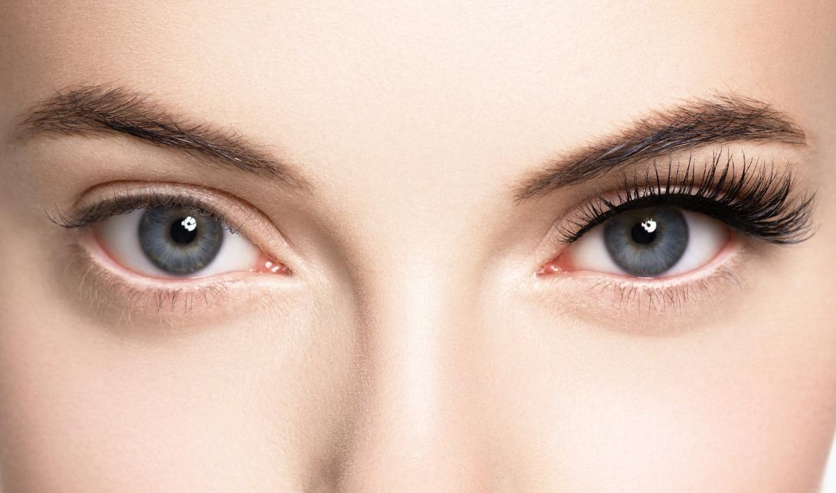 O femeie cu gene false la ochiul drept, cum privești spre poză. La ochiul stâng are genele naturale. În poză se poate observa diferența înainte și după aplicarea genelor false.