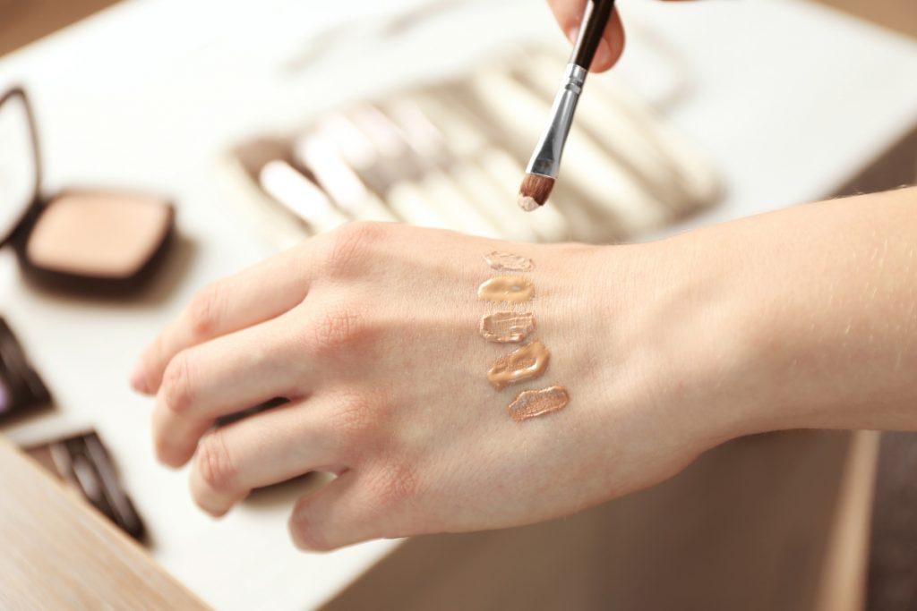 O femeie și-a aplicat pe mână cu o pensulă subțire diferite culori de fond de ten. culori
