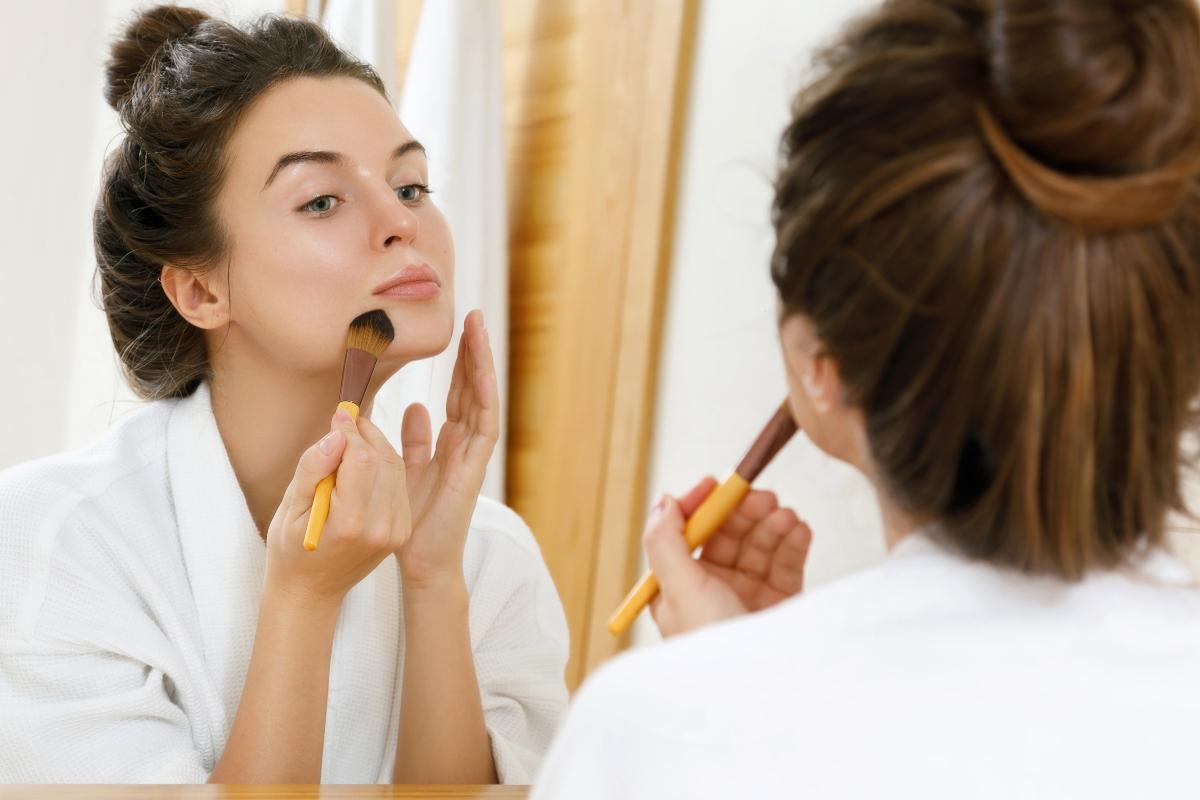 O femeie are părul strâns într-un coc, este îmbrăcată într-un halat alb de baie, îți aplică fond de ten cu o pensulă subțire.