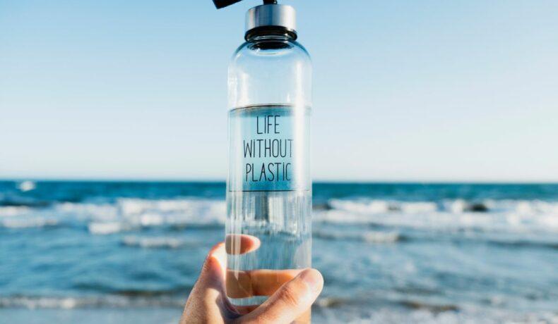 Mâna unui bărbat care ține un recipient de apă reutilizabil, în timp ce în fundal se vede marea.