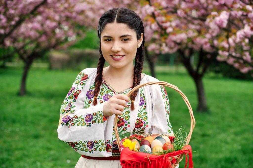 Femeie româncă într-o livadă cu cireși care ține în mână un coșuleț cu ouă vopsite pentru a prezenta cum se sărbătorește Paștele în România față de alte țări