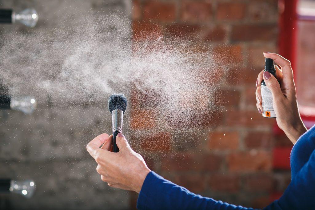 femeie care pulverizează o soluție de curățare pe o pensulă de machiaj
